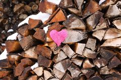 Coeur rose sur la pile de bois de chauffage Photo stock