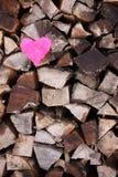 Coeur rose sur la pile de bois de chauffage Photographie stock libre de droits