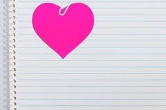 Coeur rose sur le papier de cahier Photo stock