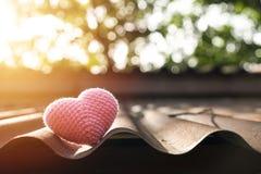 Coeur rose tricotant sur le toit image stock