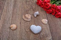 Coeur, roses et coquilles blancs sur un fond en bois Photographie stock libre de droits