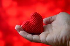 Coeur rouge à disposition avec le fond rouge Photographie stock libre de droits