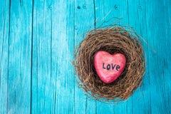 Coeur rouge à l'arrière-plan en bois de nid et de turquoise dans le style campagnard Images stock