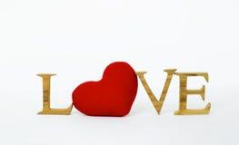 Coeur rouge avec amour en bois sur le fond blanc Images stock