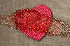 Coeur rouge avec beaucoup de perles sur le tissu rugueux Photo libre de droits