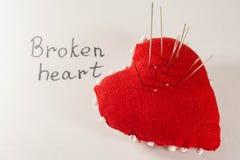 Coeur rouge avec des aiguilles dans lui sur le fond et l'inscription blancs Images libres de droits