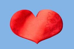 Coeur rouge avec des flocons de neige d'isolement sur un fond bleu Photo libre de droits