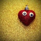 Coeur rouge avec des yeux sur le brillant lumineux de fond d'or Photo libre de droits