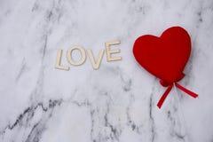 Coeur rouge avec l'amour de mot sur un fond de marbre Image stock