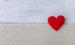 Coeur rouge avec l'espace sur le tissu de toile et le fond en bois blanc Photos libres de droits