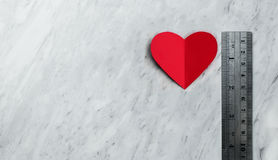 Coeur rouge avec la règle sur le fond de marbre blanc Photo stock