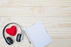 Coeur rouge avec le casque, le stylo et la note vide sur la table en bois pour v Photographie stock libre de droits