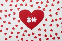 Coeur rouge avec le puzzle de deux blancs encerclé avec de petits coeurs Image stock