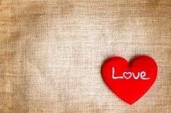 Coeur rouge avec le texte d'amour sur le fond de texture de toile à sac de jute Image libre de droits