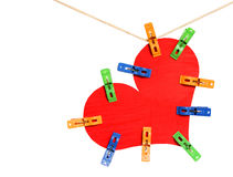 Coeur rouge avec les pinces à linge colorées accrochant sur la corde à linge Image libre de droits