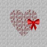 Coeur rouge avec un arc rouge Photographie stock libre de droits