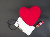 Coeur rouge avec une carte et une clé sur un fond noir Photo stock