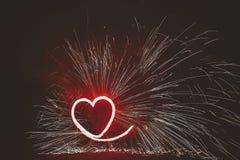 Coeur rouge brûlant avec des étincelles, exposition étonnante du feu au fest de nuit Photographie stock libre de droits