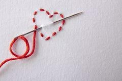 Coeur rouge brodé sur une fin blanche de tissu  Photos stock