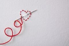Coeur rouge brodé sur une vue supérieure de tissu blanc Image stock