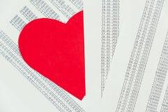 Coeur rouge caché parmi les papiers Photographie stock