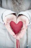 Coeur rouge chez des mains de la femme Photo stock