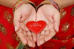 Coeur rouge chez des mains de la femme photos stock