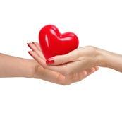 Coeur rouge chez des mains de la femme et d'homme, d'isolement sur le blanc Photos stock