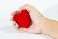Coeur rouge chez la main de la femme photographie stock