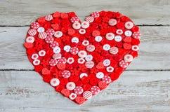 Coeur rouge couvert de boutons colorés Photo stock