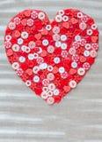 Coeur rouge couvert de boutons colorés Photographie stock