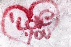 Coeur rouge criqué sur le mur en béton Photo stock