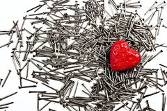Coeur rouge d'amour sur la pile des clous de fer Photos libres de droits