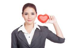 Coeur rouge d'exposition asiatique de femme d'affaires à côté de son visage Images stock