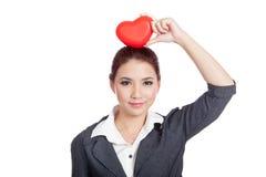 Coeur rouge d'exposition asiatique de femme d'affaires au-dessus de sa tête Image stock