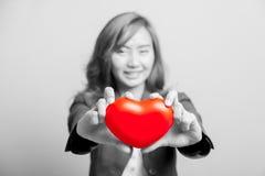 Coeur rouge d'exposition asiatique de fille avec des les deux foyer de main au coeur Image stock