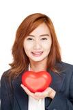 Coeur rouge d'exposition asiatique heureuse de femme d'affaires sur sa main de paume Photographie stock