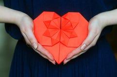 Coeur rouge d'origami dans des mains du ` s de fille Image stock