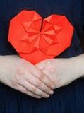 Coeur rouge d'origami dans des mains du ` s de fille Images libres de droits