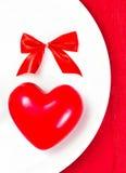 Coeur rouge d'un plat blanc de plat sur la serviette de fête avec l'arc rouge. Images libres de droits