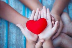 Coeur rouge dans des mains d'enfant et de parent avec l'amour et l'harmonie Photo stock