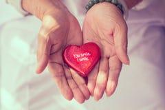 Coeur rouge dans des mains de l'aîné Photo stock
