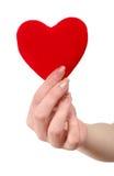 Coeur rouge dans des mains femelles Photos stock
