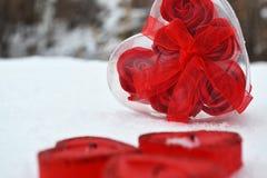 Coeur rouge dans la neige fondue trois bougies rouges sous forme de coeur images stock