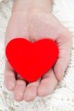 Coeur rouge dans la paume d'un homme Image stock