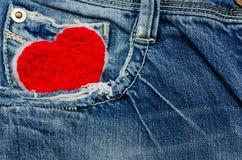 Coeur rouge dans la poche de treillis Photos libres de droits