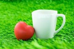 Coeur rouge dans la tasse de café sur l'herbe, concept d'amour Photo libre de droits