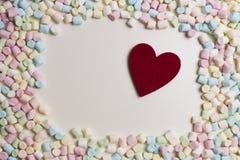 Coeur rouge dans le cadre de mini guimauves colorées comme fond Vue supérieure Image stock