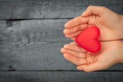 Coeur rouge dans les mains Photographie stock libre de droits