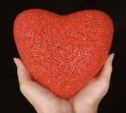Coeur rouge dans les mains de femme Photo stock